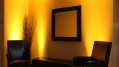 The image shows our amber up-lighting warms and breathes life into a stark seating area for a special corporate event.