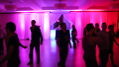 Image shows how lighting the room with warm colours enhances the social dancing at this West Coast Swing dance event. Photo by Artistic Illumination.